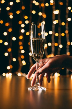 cropped image of woman touching glass of champagne on garland light background, christmas concept