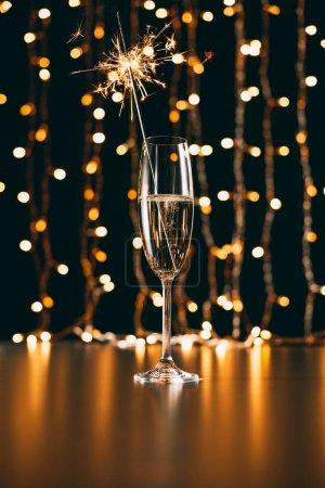 champagne avec étincelle de Noël sur fond de guirlande lumière