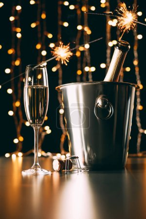 champagne with bengal lights on garland light background, christmas concept