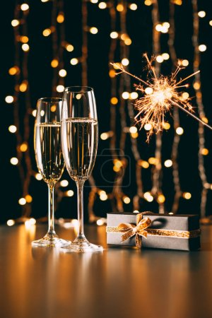 glasses of champagne, present and christmas sparkle on garland light background, christmas concept