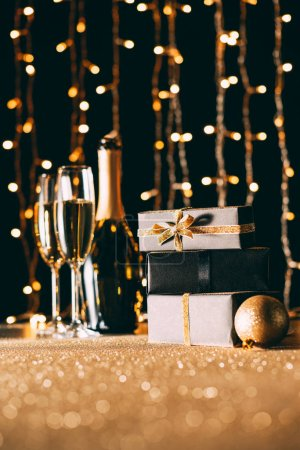 surface level of champagne and presents on garland light background, christmas concept