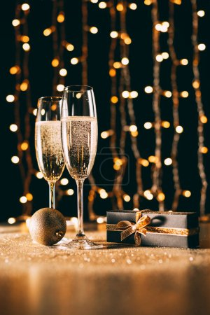 Photo for Glasses of champagne, gift and bauble on garland light background, christmas concept - Royalty Free Image