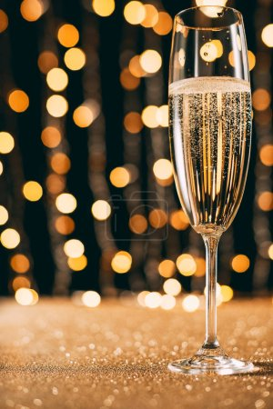 Photo for One glass of champagne on garland light background, christmas concept - Royalty Free Image