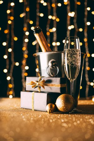 champagne in bucket and presents on garland light background, christmas concept