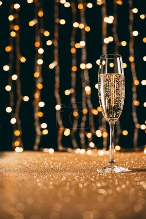 surface level of one glass of champagne on garland light background, christmas concept