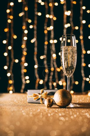 glass of champagne, golden baubles and present on garland light background, christmas concept