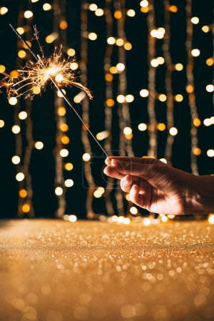 cropped image of woman holding christmas sparkle on garland light background