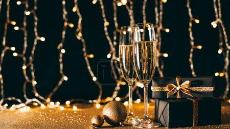 Foto de Copas de champagne, adornos y regalos en garland luz de fondo, concepto de Navidad - Imagen libre de derechos