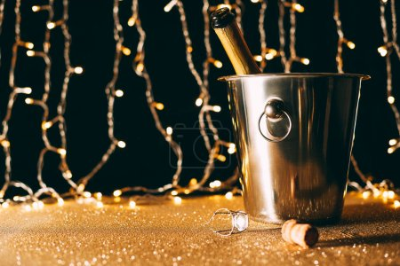 champagne bottle in bucket on garland light background, christmas concept