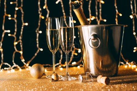 Photo for Two glasses and champagne bottle in bucket on garland light background, christmas concept - Royalty Free Image