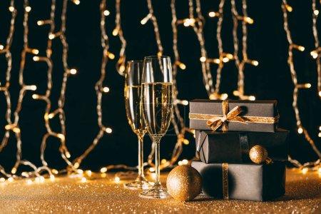 Photo pour Cadeaux de Noël et verres de champagne sur fond de guirlande lumière - image libre de droit