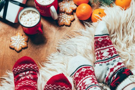 Photo for Cropped shot of women in winter socks at background with cups of cocoa with marshmallows - Royalty Free Image