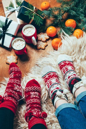 Photo for Cropped shot of women in winter socks at background with wrapped christmas presents and cups of hot chocolate with marshmallows - Royalty Free Image