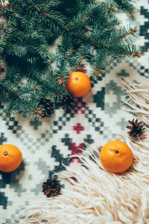 top view of pine tree branches, pine cones and fresh tangerines on blanket backdrop