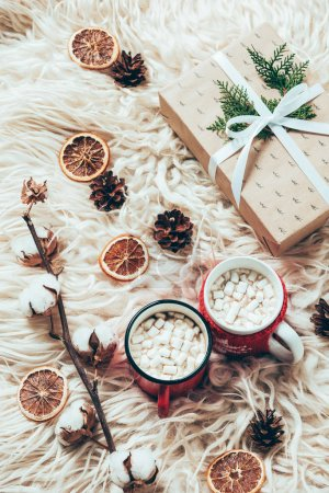 flat lay with cup of cocoa with marshmallows, wrapped christmas present and cotton twig on woolen background