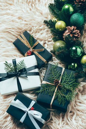 flat lay with Christmas festive wreath and wrapped gifts on woolen backdrop