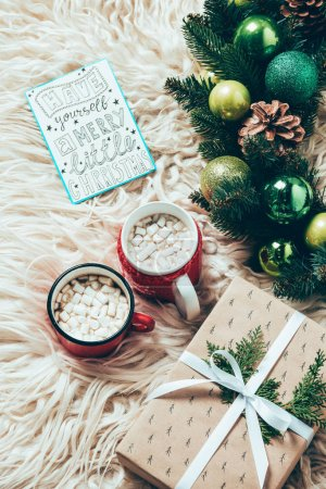top view of christmas wreath, cups of cocoa drinks with marshmallows and postcard with have yourself marry little christmas lettering on woolen backdrop