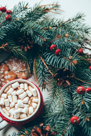 top view of pine tree branches, cookies and cup of hot chocolate with marshmallows on white surface, christmas breakfast concept
