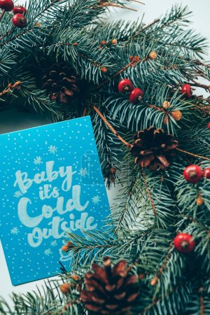 top view of pine tree branches and winter postcard with baby its cold outside lettering on white tabletop