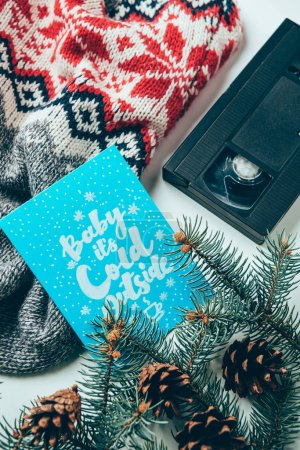 top view of video cassette, sweater and postcard with baby its clod outside lettering on white surface