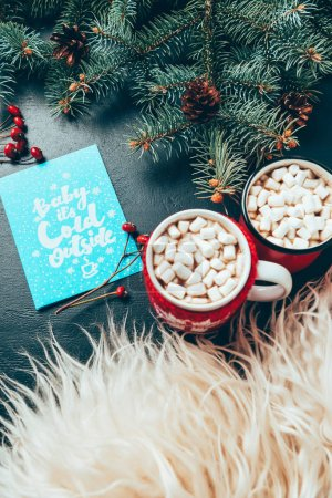top view of cups of hot drinks with marshmallows, pine tree branches and postcard with baby its cold outside lettering on black surface, christmas and new year holidays concept