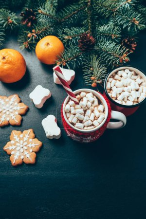 Photo for Top view of cups of hot drinks with marshmallows, cookies and tangerines on black surface, christmas breakfast concept - Royalty Free Image