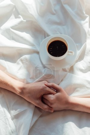 cropped shot of couple holding hands on white bed sheet with cup of aromatic coffee