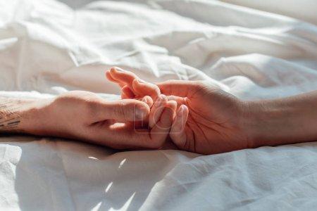 vue partielle du couple en direct tenue hads en position couchée dans le lit ensemble