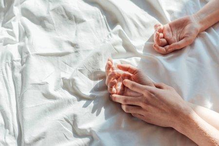 Foto de Vista parcial de pareja en dispone de explotación directo mientras se está acostado en la cama juntos - Imagen libre de derechos