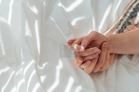 Photo pour Vue partielle du couple aimant tenant la main tout en étant couché sur un drap de lit blanc - image libre de droit
