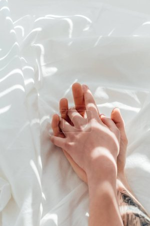 Photo for Partial view of loving couple holding hands while lying on white bed sheet - Royalty Free Image