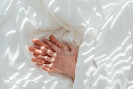 partial view of loving couple holding hands while lying under blanket together