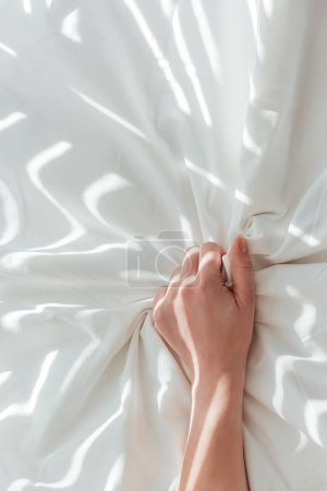 partial view of woman holding white bed sheet while lying in bed