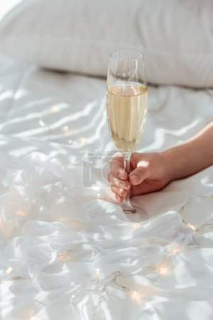 cropped shot of woman holding glass of champagne in hand on white bed sheet with garland