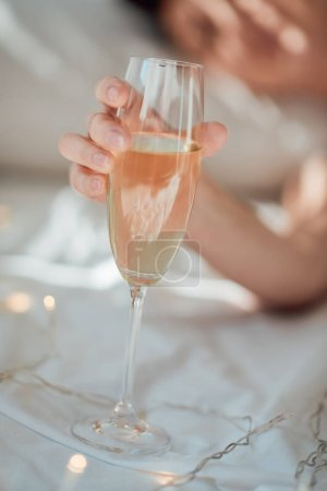 partial view of woman holding glass of champagne on white bed sheet with garland