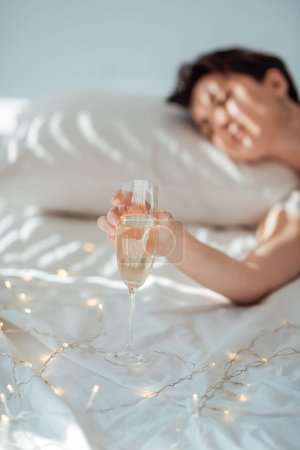 Photo for Close up view of woman holding glass of champagne on white bed sheet with garland - Royalty Free Image