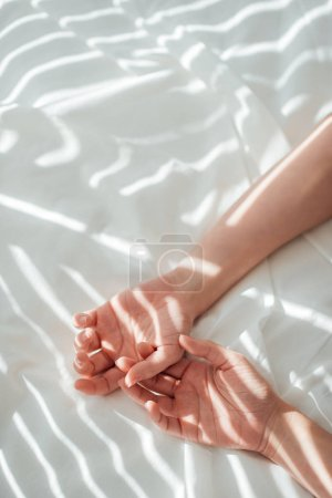 cropped shot of female hands on white bed sheet