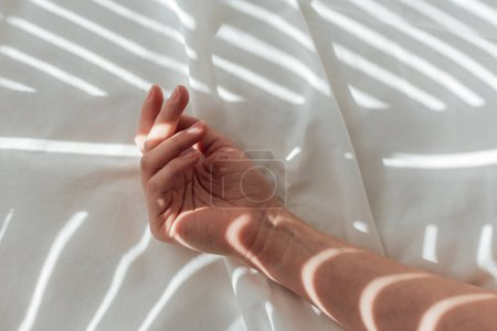 Photo for Cropped shot of female hand on white bed sheet - Royalty Free Image