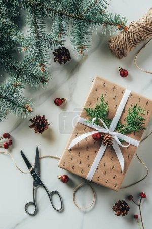 Photo for Top view of christmas gift box with fir branches and scissors on marble table - Royalty Free Image