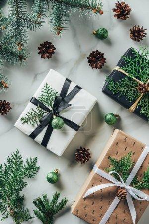 Photo pour Lay plat avec cadeaux, boules de Noël et des pommes de pin sur table de marbre - image libre de droit