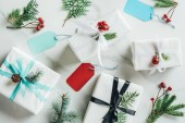 flat lay with christmas gifts, fir branches, decorative berries and tags on marble background
