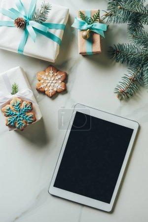 Foto de Presenta la vista superior de Navidad, galletas de copo de nieve y tableta digital con pantalla en blanco sobre fondo de mármol - Imagen libre de derechos