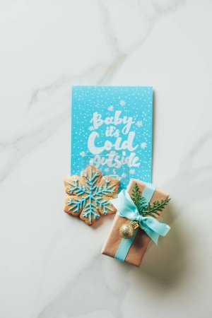 "top view of christmas present, snowflake cookie and greeting card with ""baby its cold outside"" lettering on marble background"