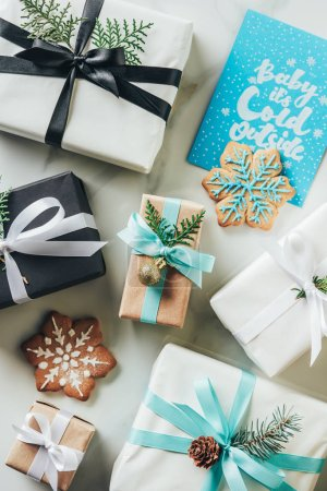 Photo pour Haut de la page vue des cadeaux de Noël, cookies de flocon de neige et carte de voeux avec «baby son froid dehors» lettrage - image libre de droit