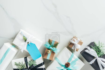 flat lay with christmas gift boxes, bows and decoration on marble background with copy space