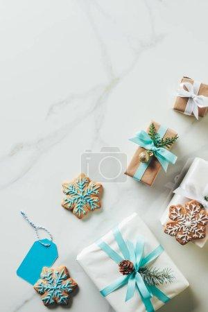 Foto de Vista superior de regalos de Navidad y las galletas de copo de nieve con formación de hielo sobre fondo de mármol con espacio de copia - Imagen libre de derechos