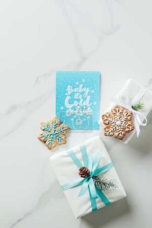 """Photo for Top view of white christmas gifts, snowflake cookies and greeting card with """"baby its cold outside"""" lettering on marble table - Royalty Free Image"""