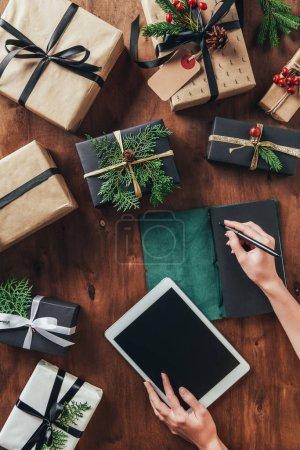 partial view of woman using tablet and writing list in diary on wooden table with christmas presents