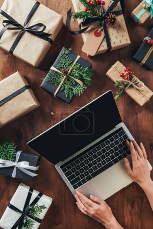 partial view of woman using laptop with blank screen on wooden table with christmas presents