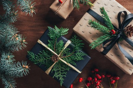 Photo for Top view of christmas gift boxes with fir branches and decorative berries on wooden background - Royalty Free Image